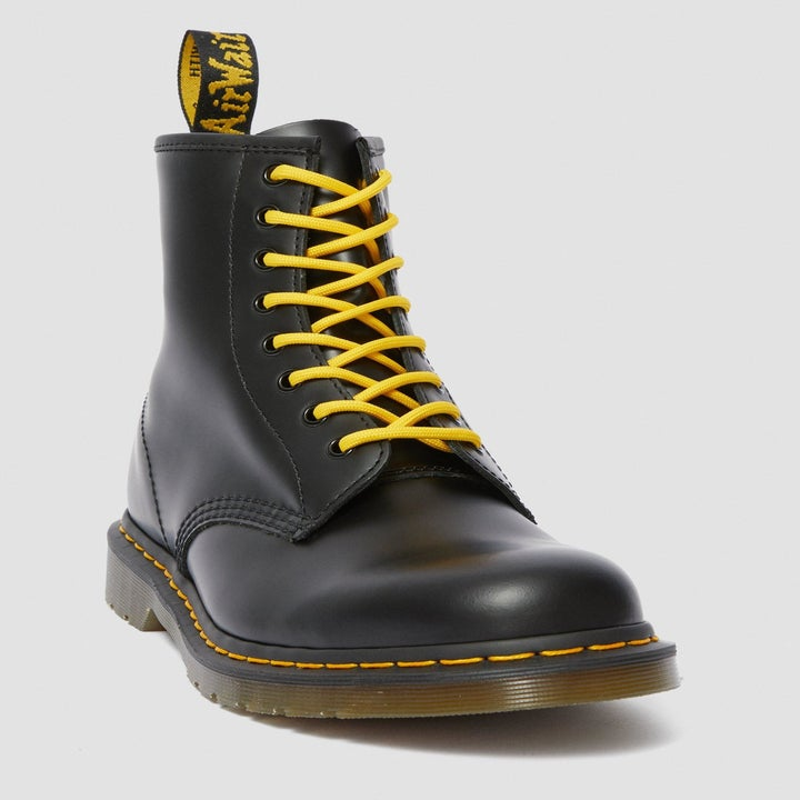 A black boot with bright yellow laces