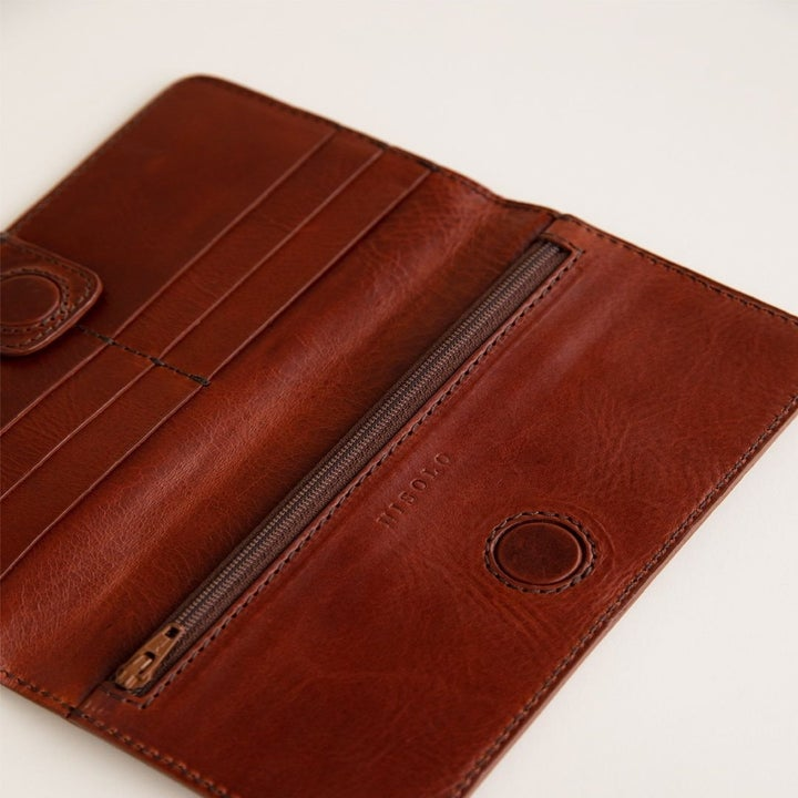 The wallet in a dark chocolate brown opened showing card holders and a zipper