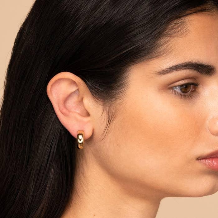 a model wearing gold dome hoop earrings