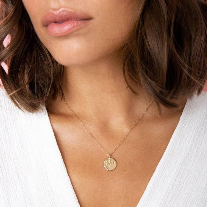 a model wearing a gold necklace with a gold pendant that has an astrological constellation etched into it