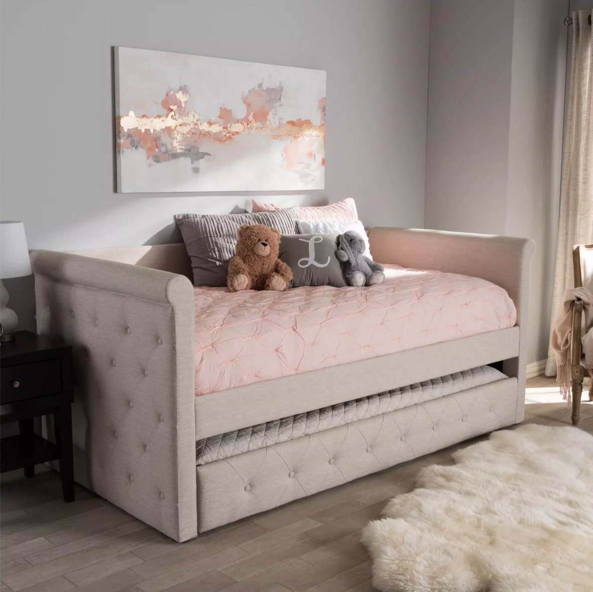 A beige tufted daybed with trundle