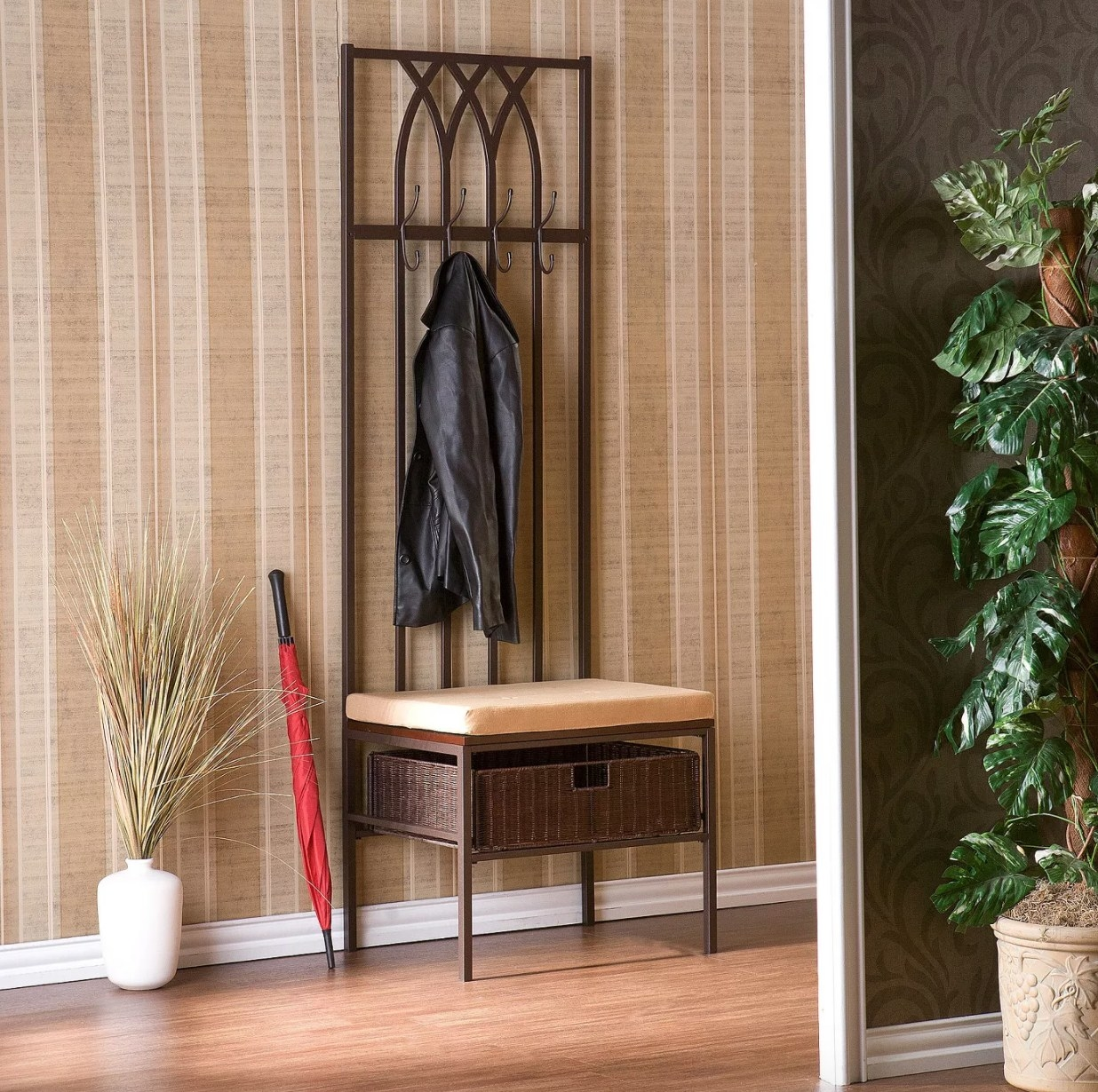 A dark brown entryway bench with cushion, storage basket, and coat hooks