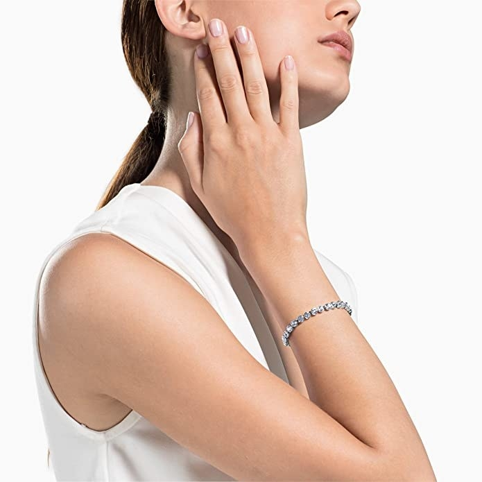 a model wearing a tennis bracelet with silver metal and white crystals