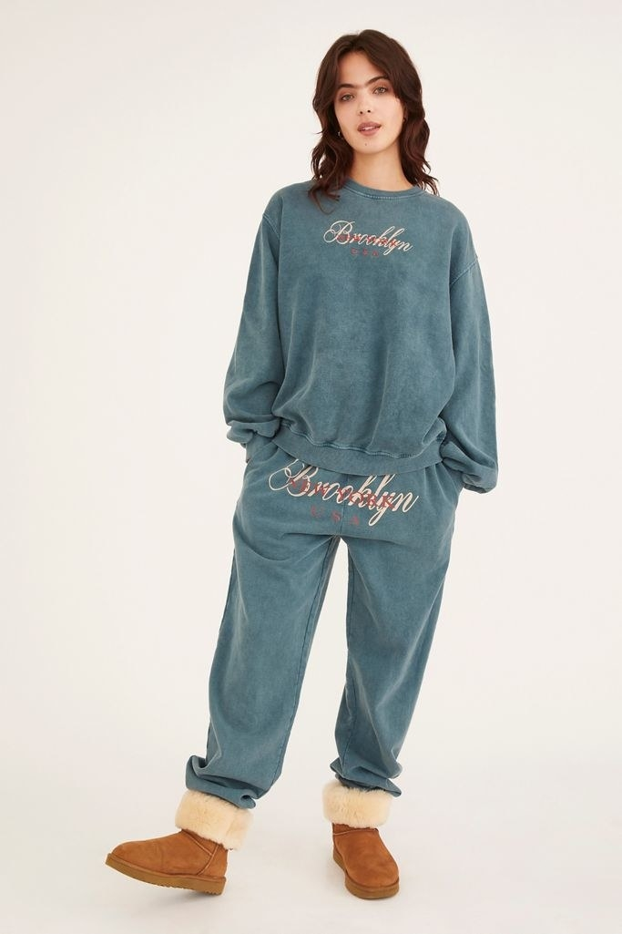 Model wearing teal-colored set with Brooklyn graphic text embroidery