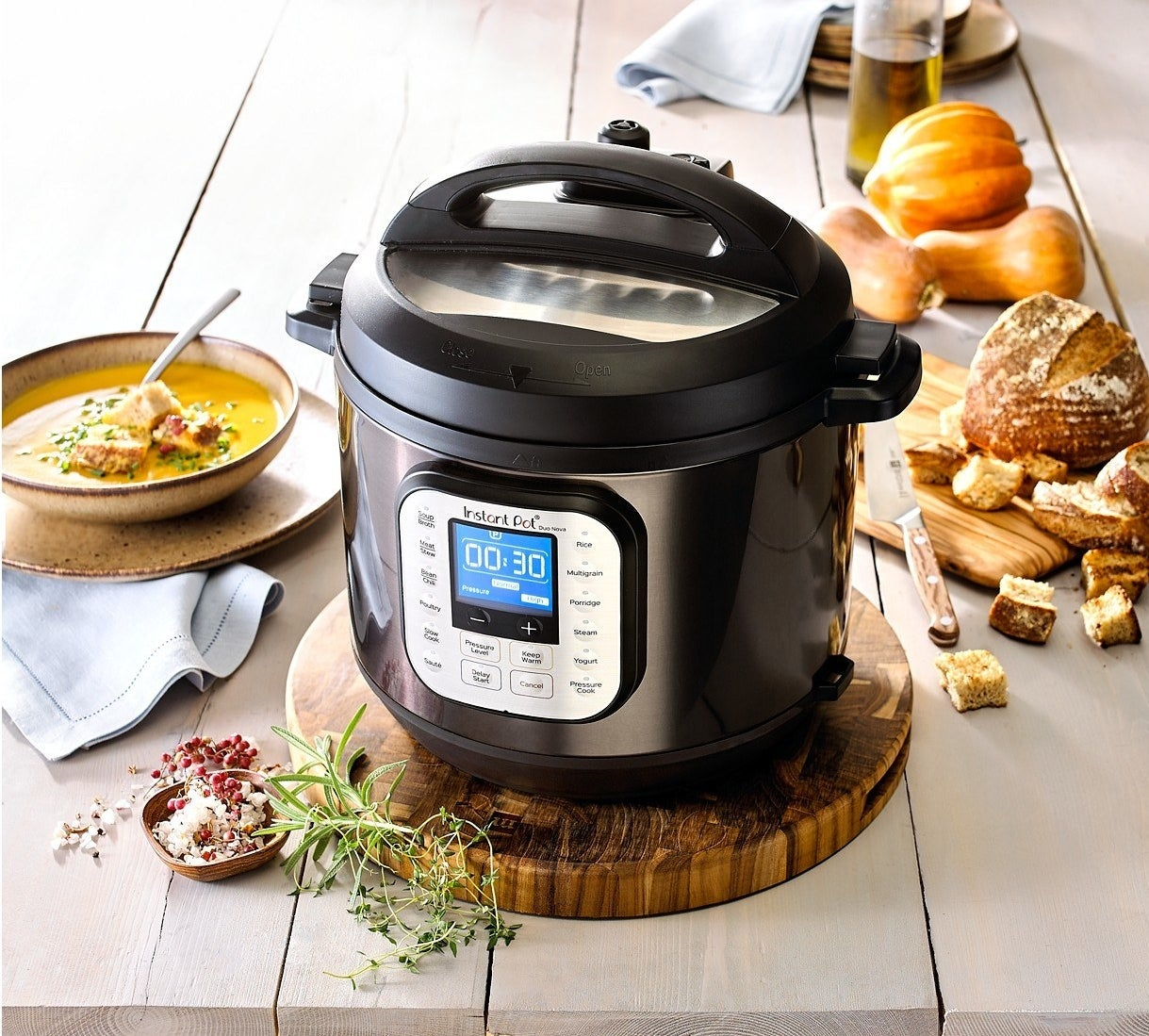 Black stainless steel Instant Pot on table next to bowl of food