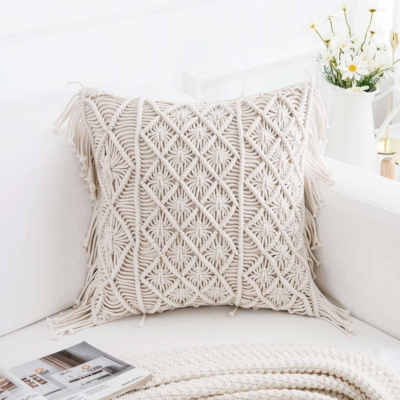 A beige macrame cushion kept on a beige couch.