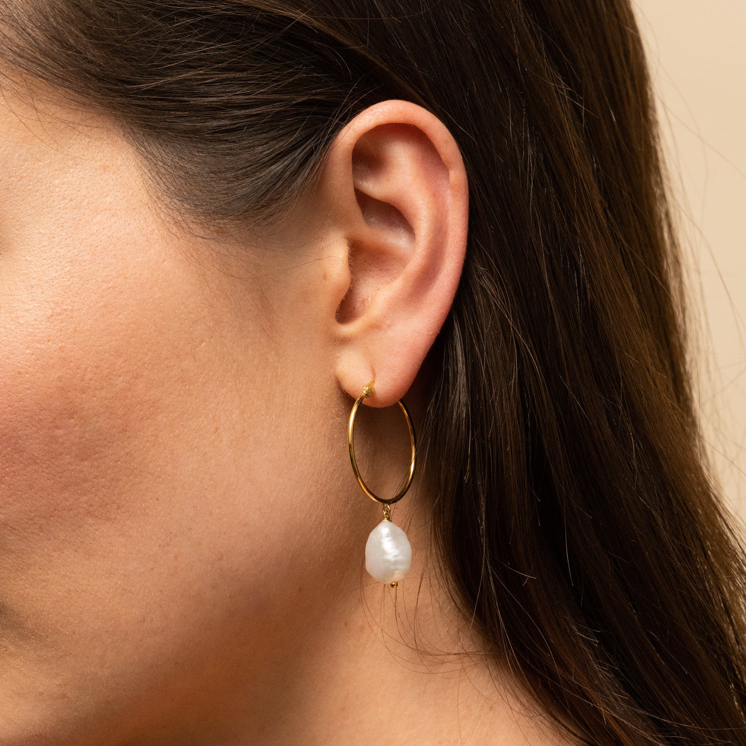 A model wearing a gold hoop earring with a large pearl on the end