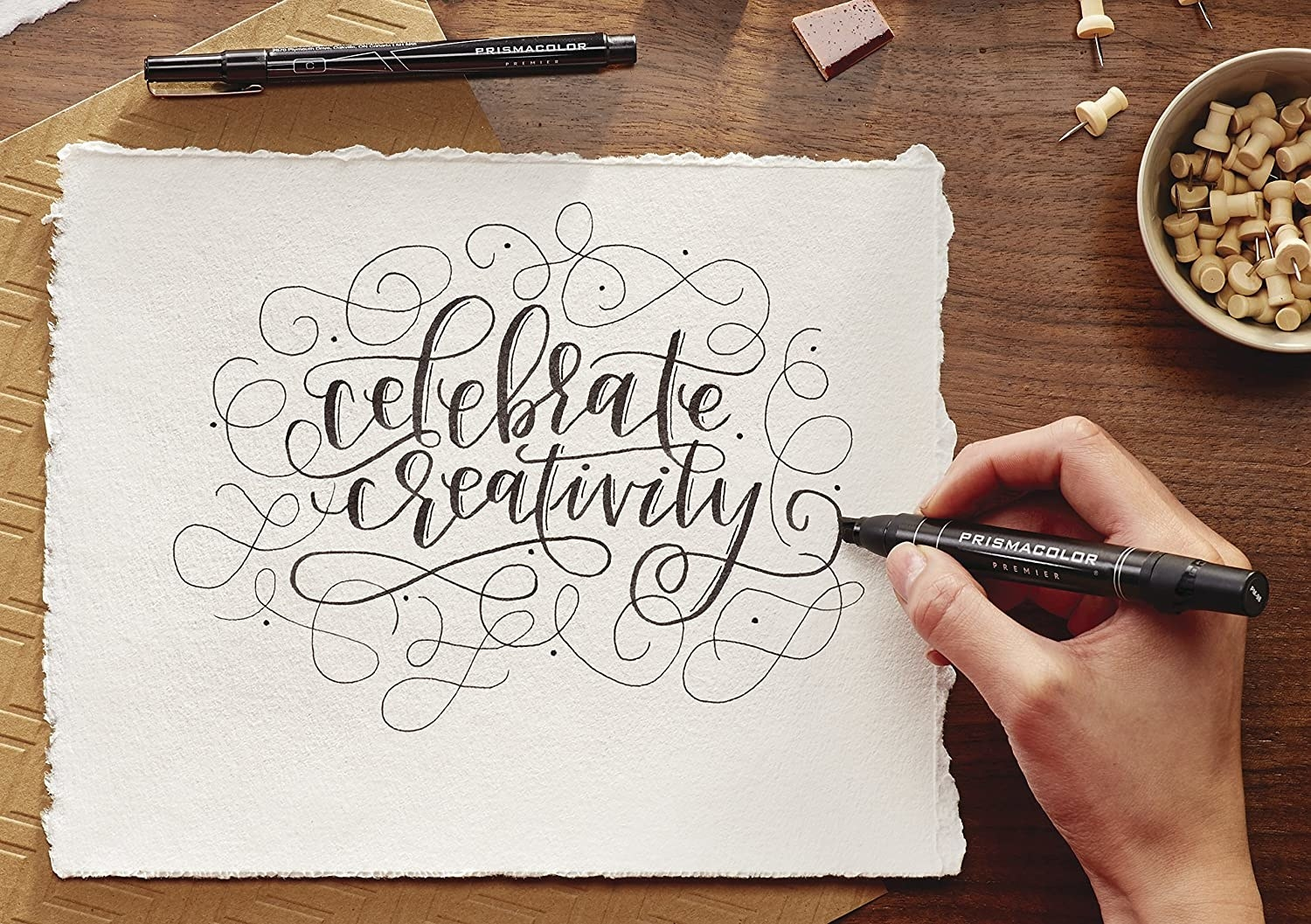 person writing celebrate creativity on a piece of paper