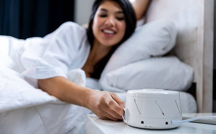a model in bed turns on their dohm classic