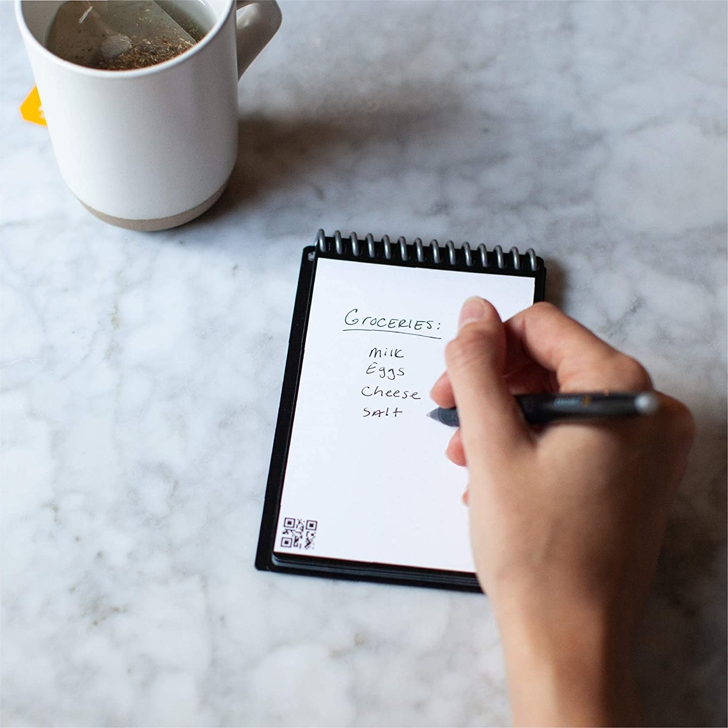 person writing a grocery list on their notepad that includes milk eggs cheese and salt