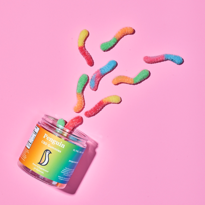 An open jar of Penguin CBD gummy worms with the different-colored gummy worms spilling out