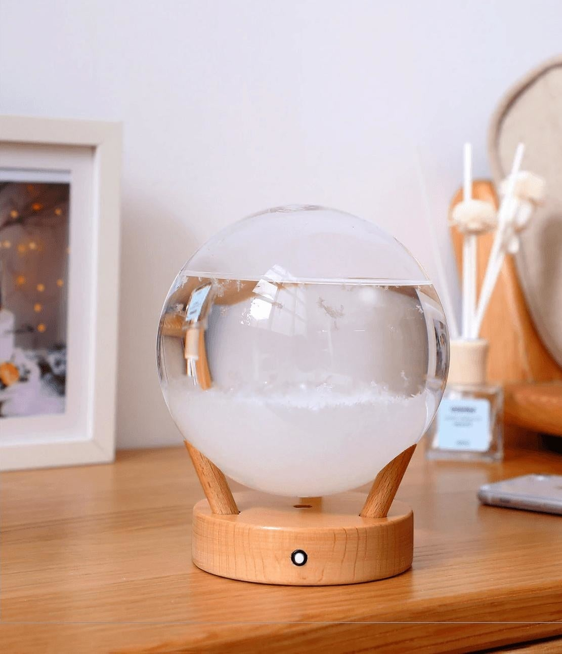 Round globe filled with water and crystal on wooden base with three legs