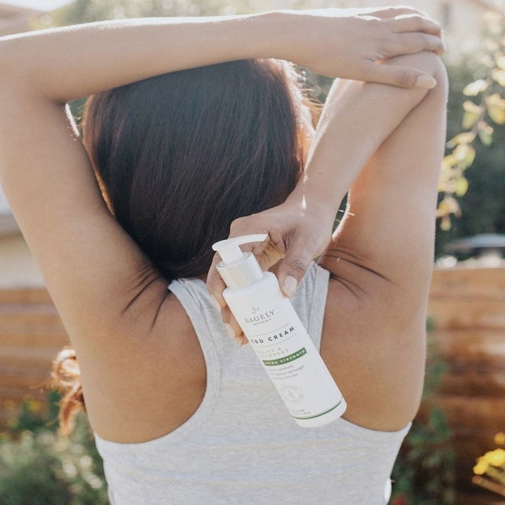 The backside view of a model doing an arm stretch and holding the Relief and Recovery CBD Cream behind their back