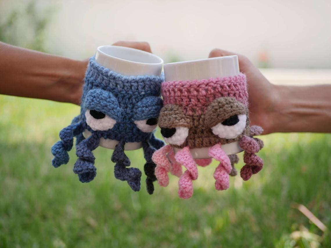 Two people holding mugs with octopus sleeves on them