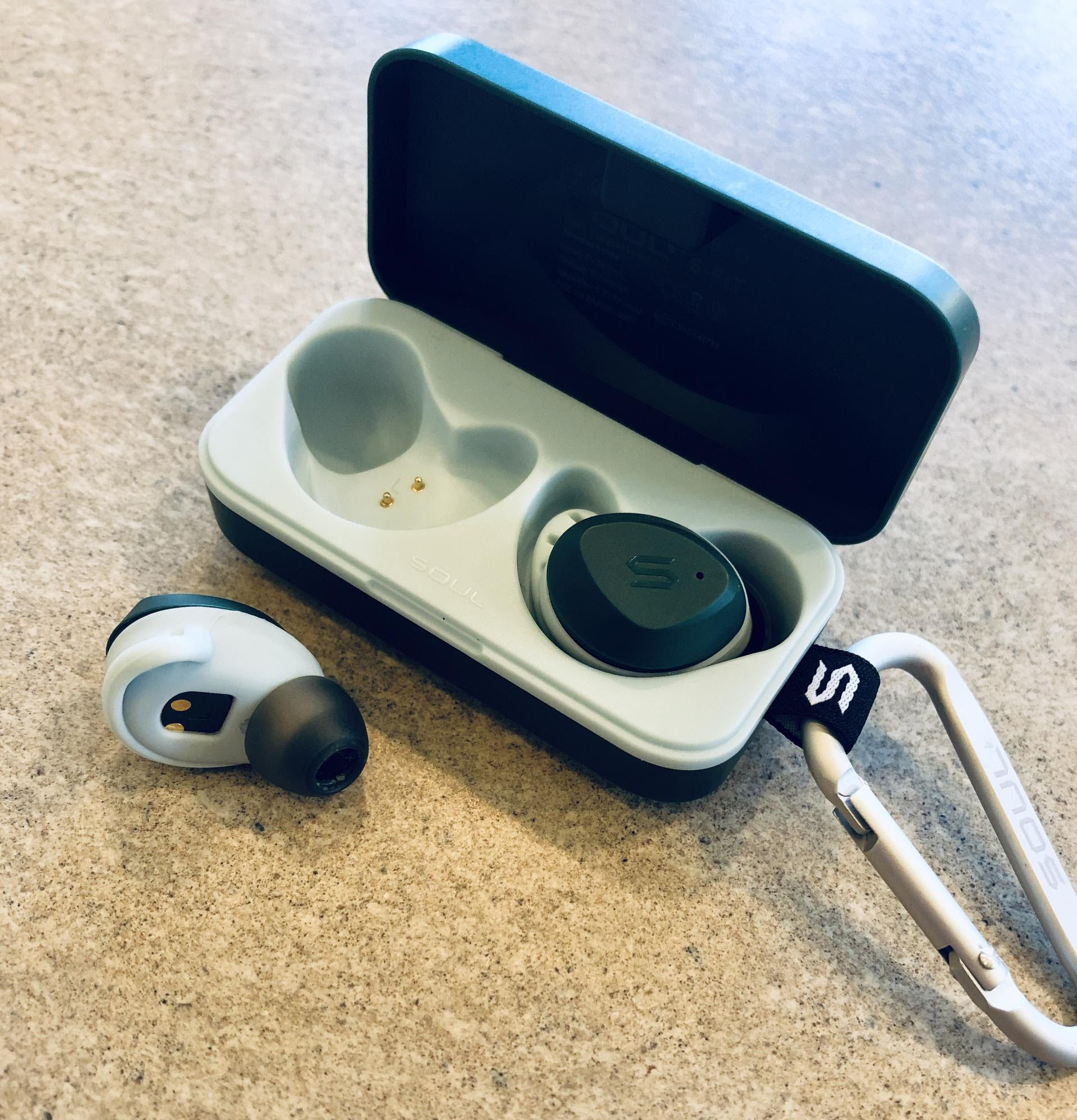 small wireless earbuds in their charging base attached to a carabiner