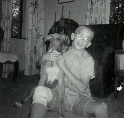 Finefrock as a child wears glasses and sits on the floor smiling and holding his dog, a boxer