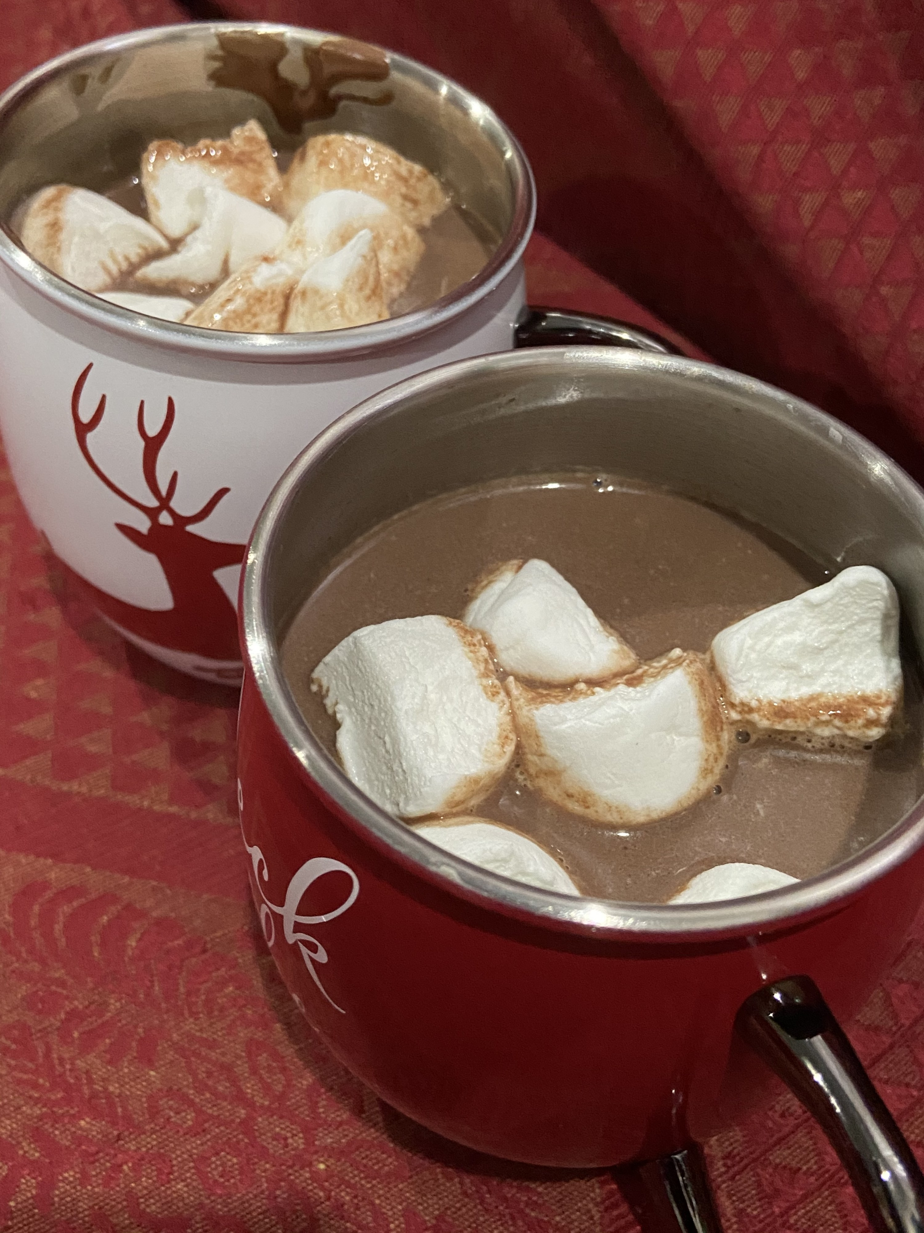 Two cups of hot chocolate with marshmallows inside