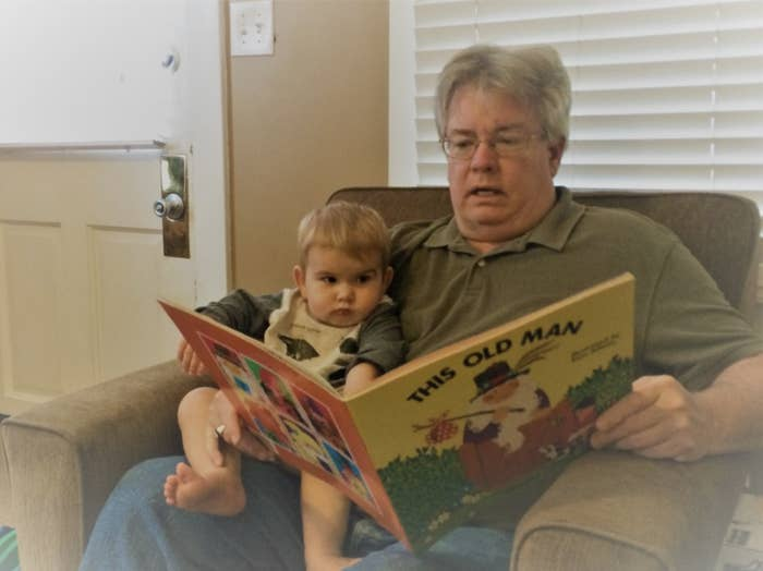 "George Finefrock sits in an armchair with his infant grandson on his lap, holding open a large picture book in front of them titled ""This Old Man"""