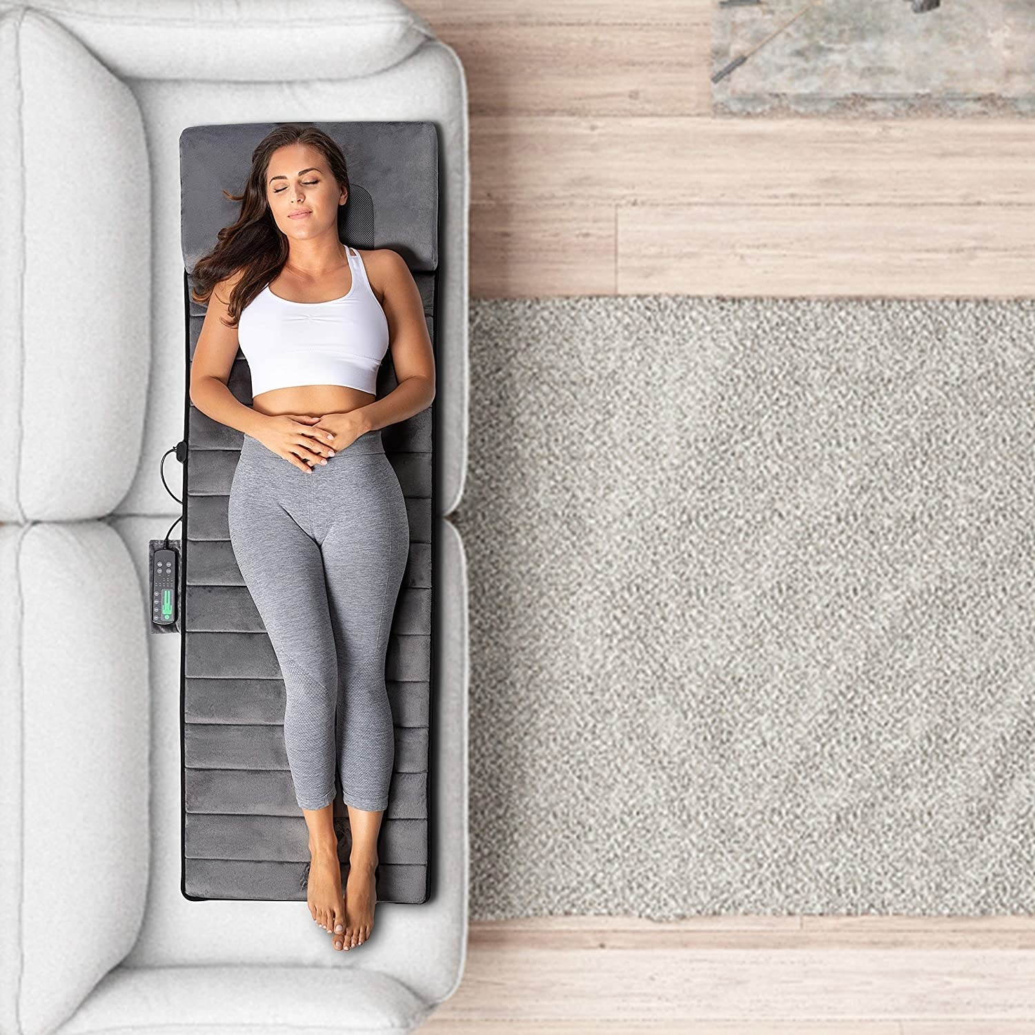 A person lying on the massage mat on their couch