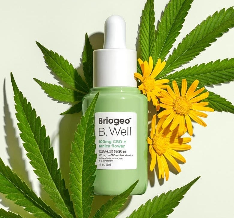 A green bottle of Briogeo B.Well skin and scalp oil surrounded by marijuana leaves and yellow arnica flowers