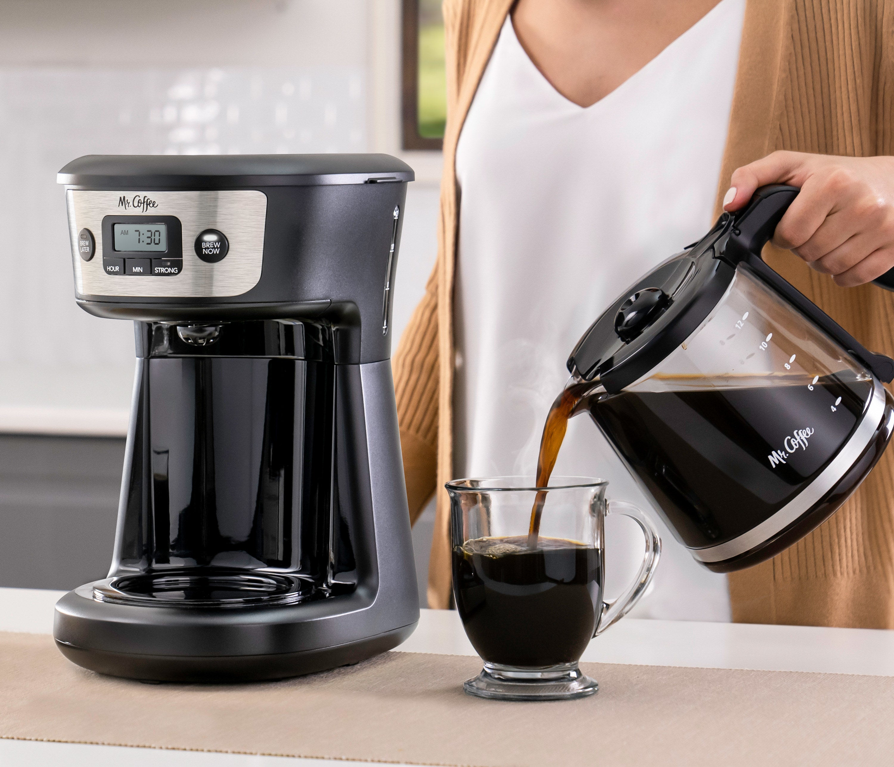 Model pouring coffee from black coffee machine