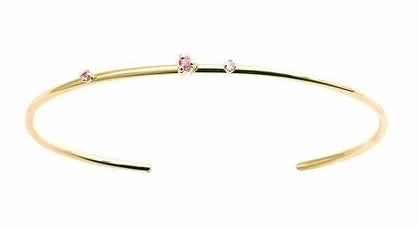 a thin gold cuff with three pink gems on the rim
