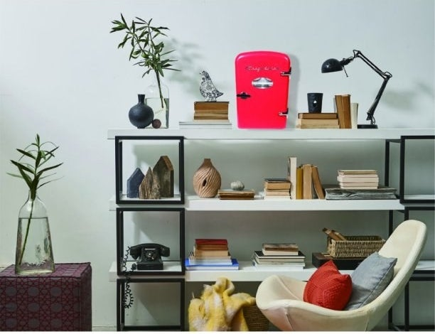 the fridge in red with silver hardware displayed on a shelf in a living room