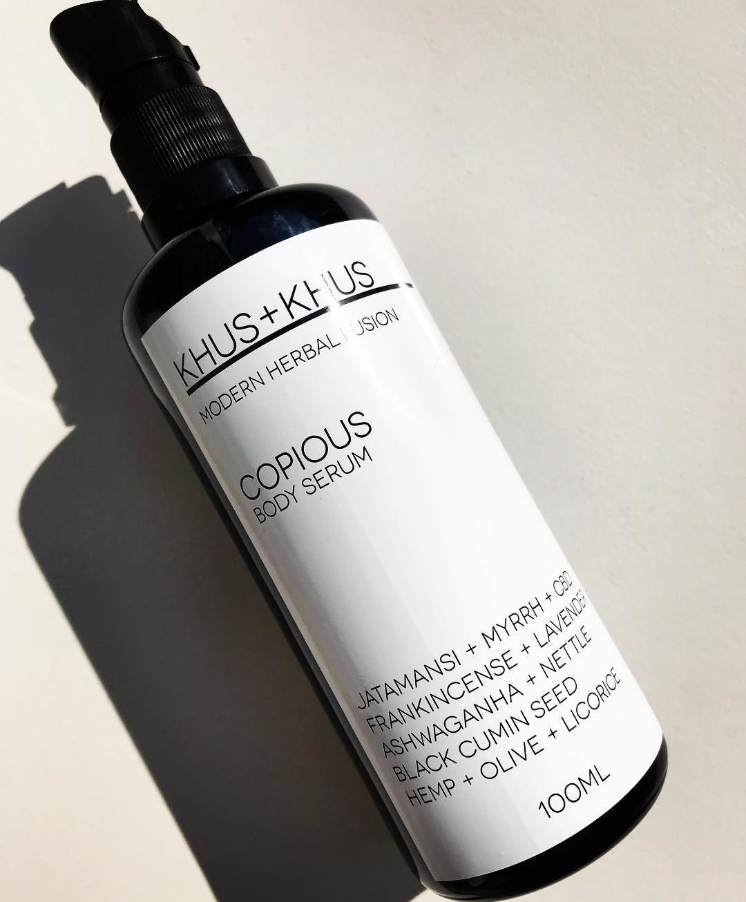 A black pump bottle with a white label of Khus + Khus Copious Body Serum