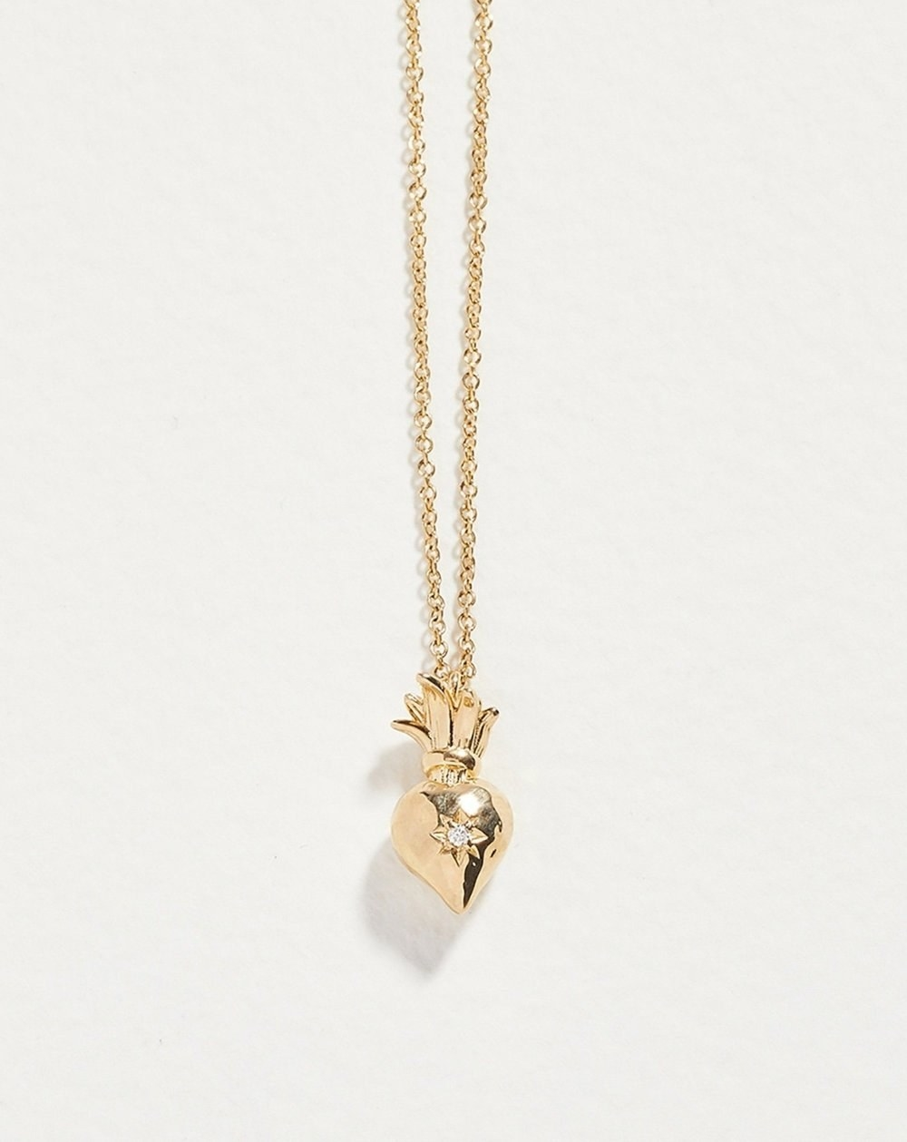 a gold sacred heart pendant with a diamond encrusted in its center on a gold chain