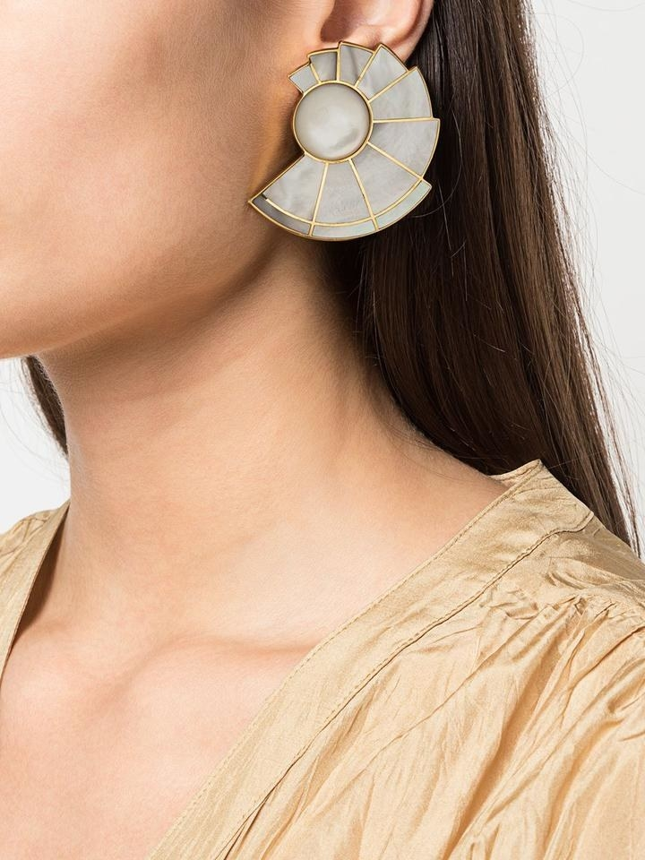 a grey and gold earring in a geometric shape