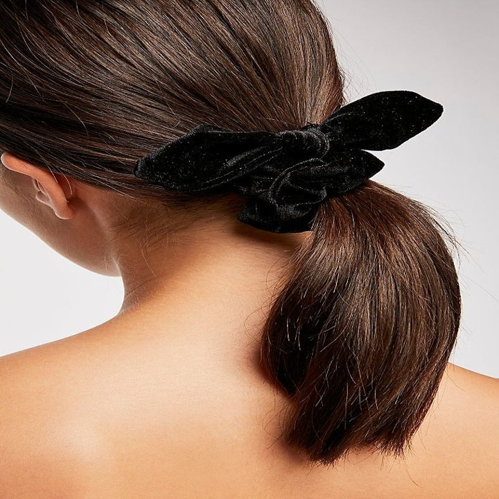 A model using the scrunchie to tie their hair back