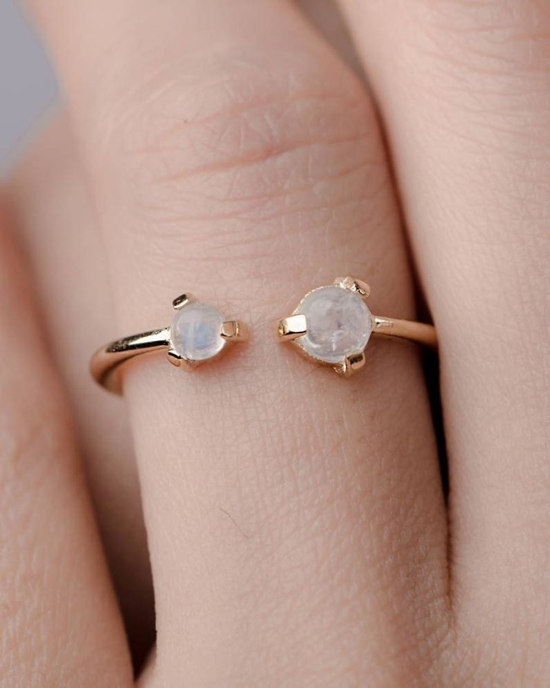a cuff ring with two moonstone gems at the cuffs
