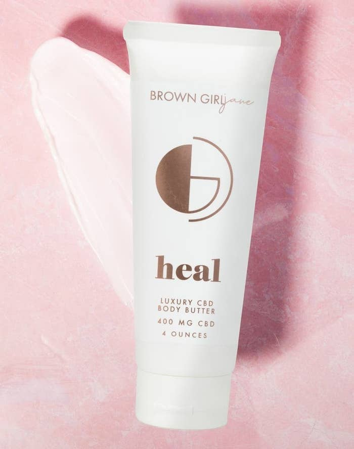 A tube of Brown Girl Jane Healy Whipped Body Butter against a pink background