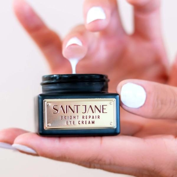 A hand dipping a finger into the Saint Jane Bright Repair Eye Cream
