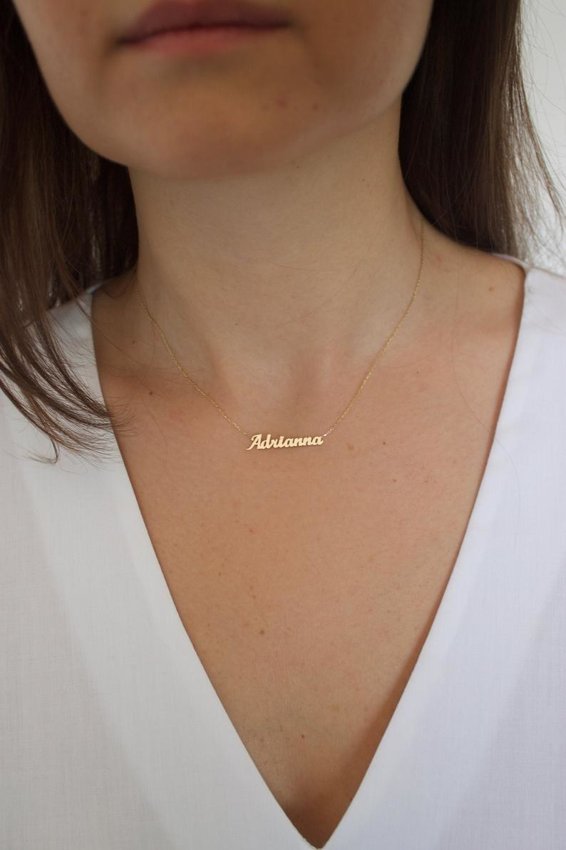 a model wearing a gold nameplate necklace that reads Adrianna in cursive