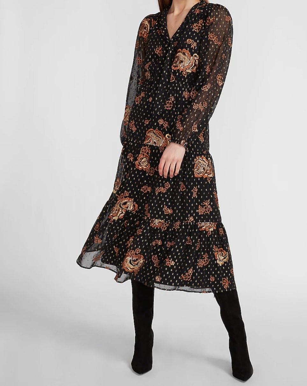 A woman wearing a boho print midi dress and black velvet boots.