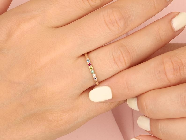 a model wearing a gold ring encrusted with different colored gems