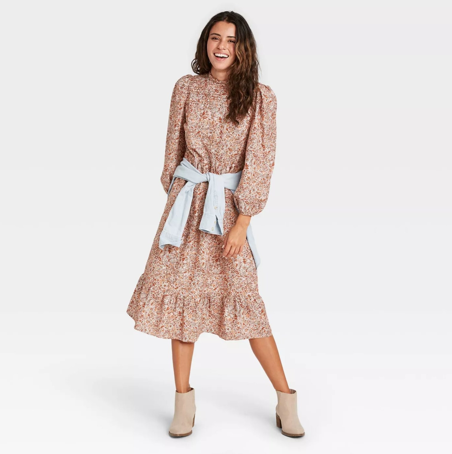 Model wearing the dress in floral pink with denim wrapped jacket wrapped around their waist