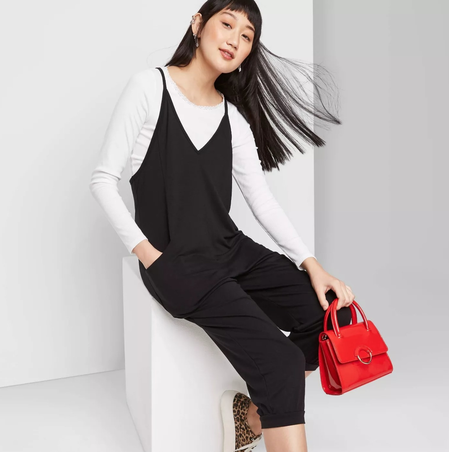 Model wearing the jumpsuit in black holding a red handbag