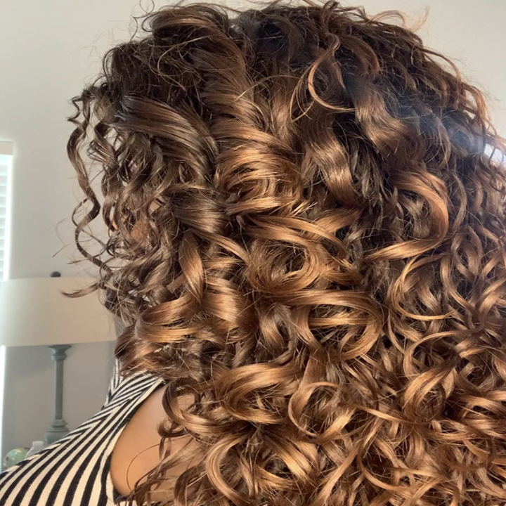 A reviewer with radiant curls after using the product