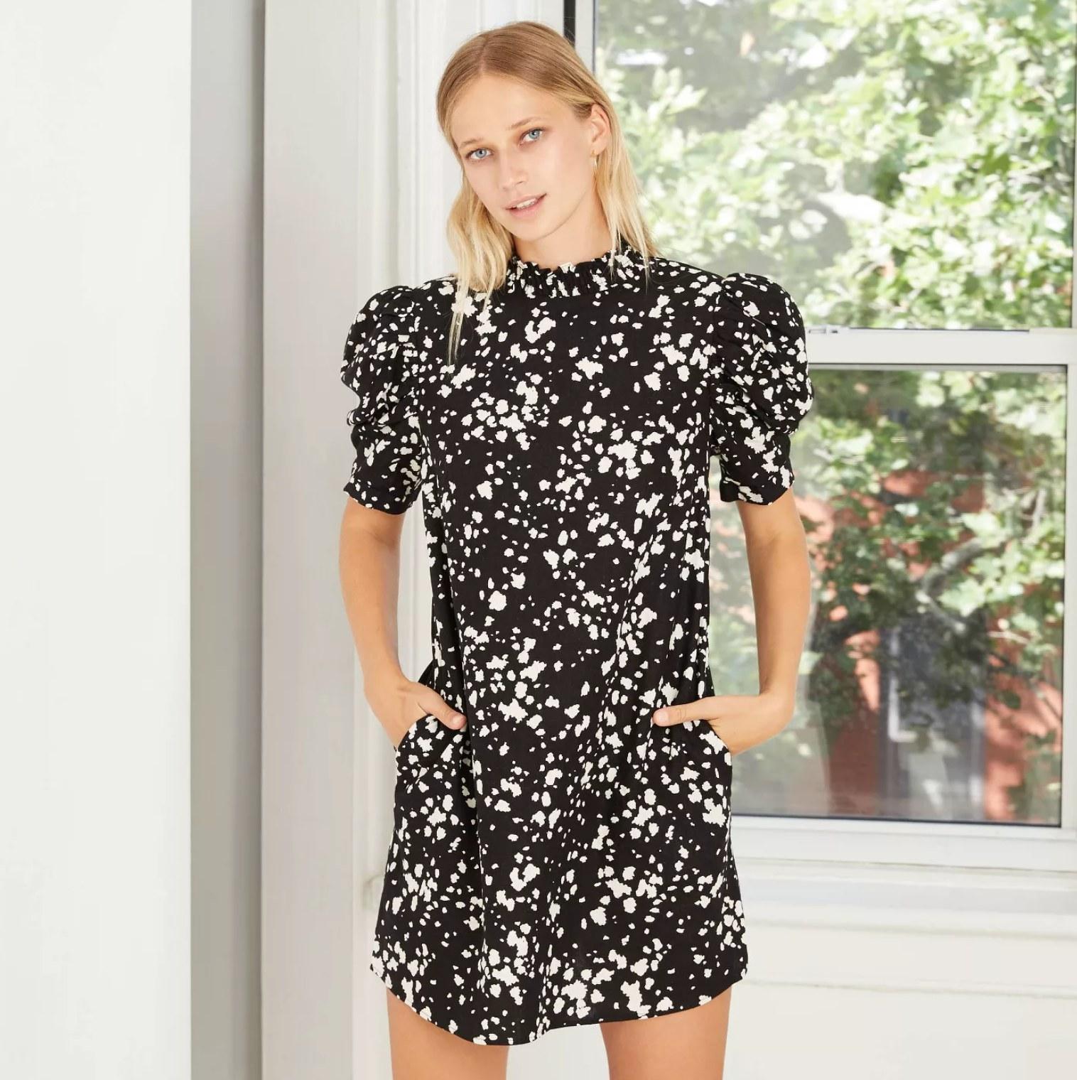 Model wearing the dress in black with white splatter pattern
