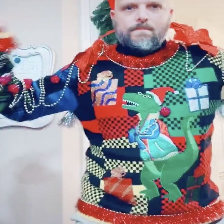 A man in a sweater with a dinosaur in a Christmas hat