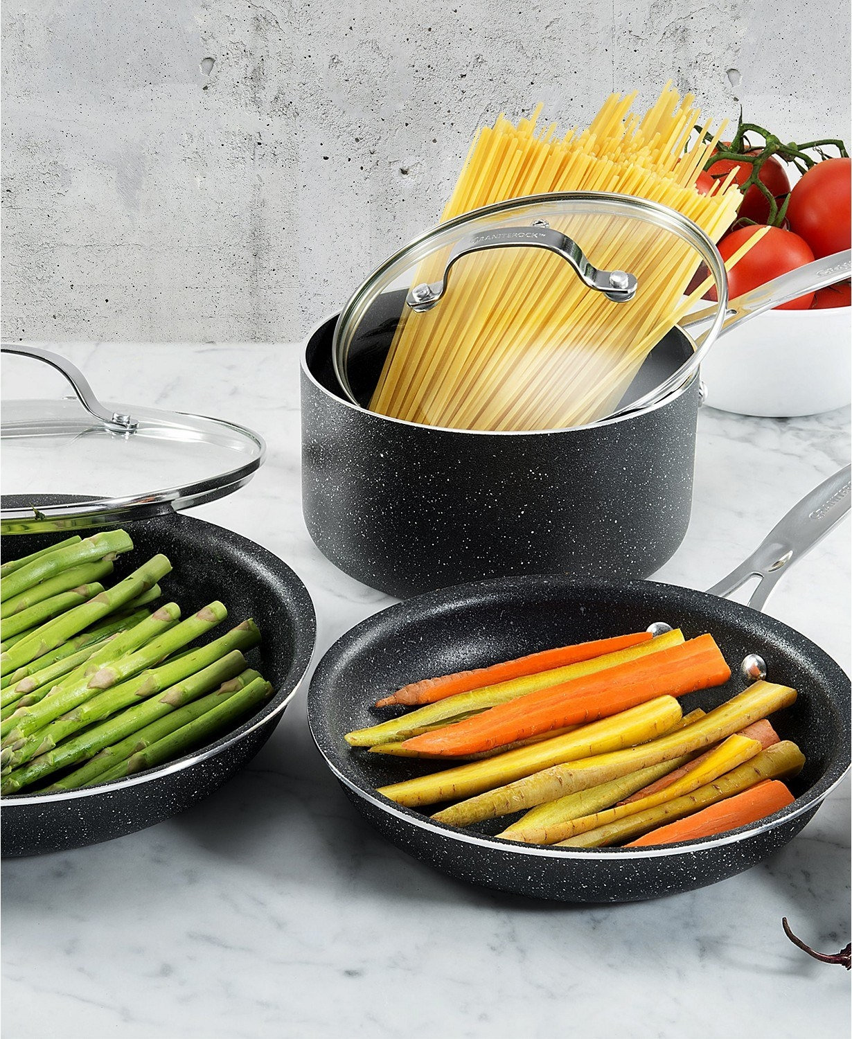 Two non-stick pans and one pot filled with veggies and pasta placed on countertop