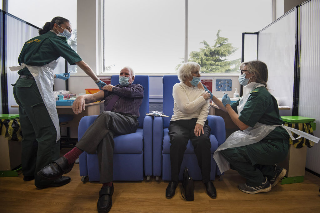 An older man and an older woman sit in cushioned seats in face masks as they receive COVID-19 vaccines from two nurses in green uniforms