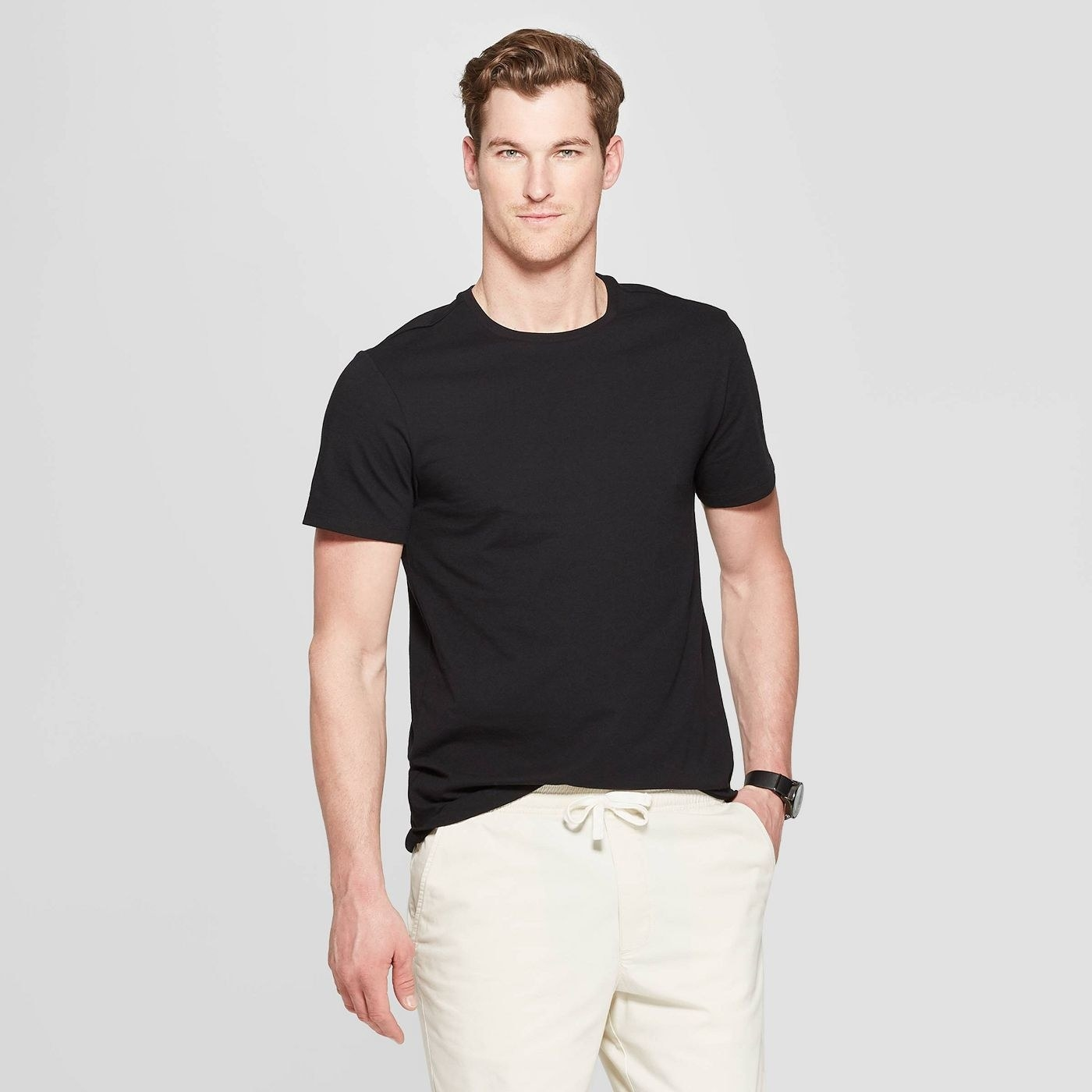 A person wearing the black t-shirt and white pants