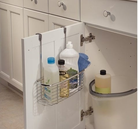 The shelf hung on a cabinet door filled with cleaning supplies
