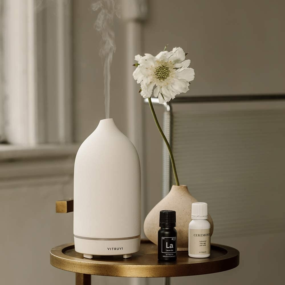 white ceramic vitruvi diffuser on a table with essential oils