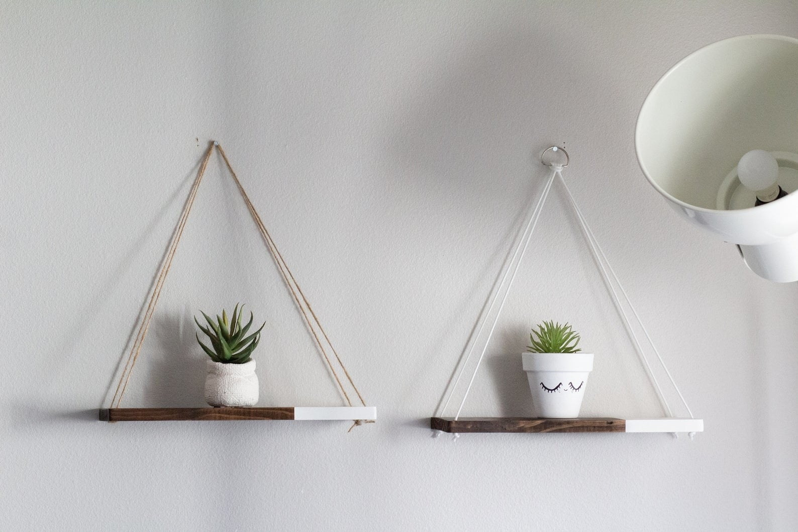two hanging wood shelves with planters on top