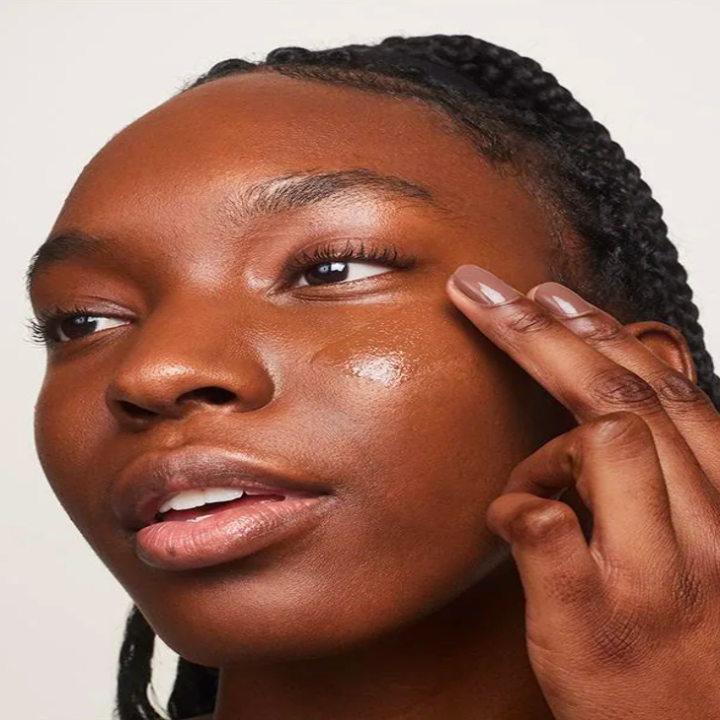 a model putting the skin enhancer makeup on their face