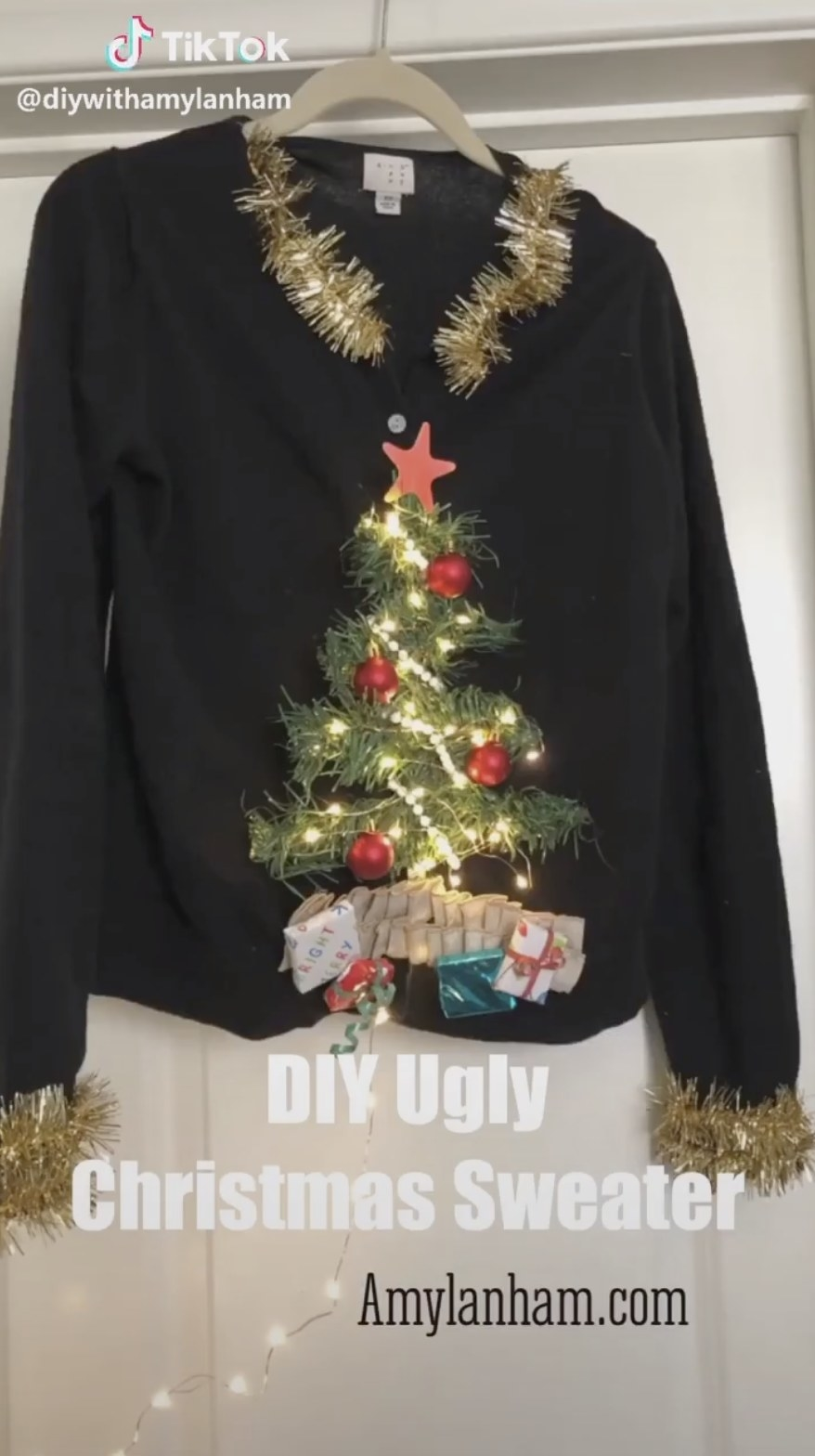 A black cardigan with a 3D Christmas tree